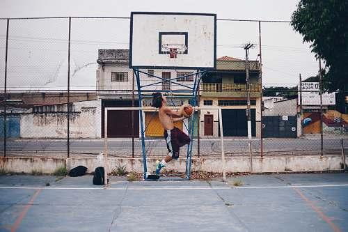 human man wearing brown shorts doing lay-up near basketball ring during daytime people