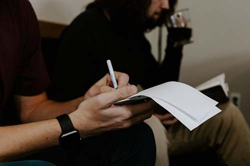 human man writing beside man people