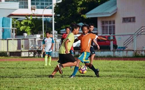football men's playing soccer during daytime soccer