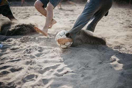 human people playing soccer on sand sphere