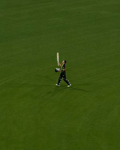 human person holding a cricket paddle in a green field people