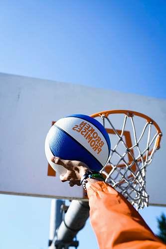 human person holding basketball facing towards basketball hoop people