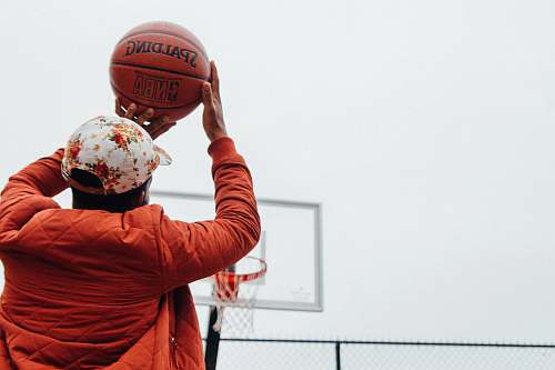 sport person holding basketball looking at basketball hoop system people
