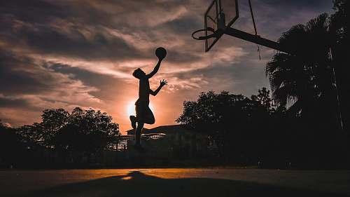human silhouette of boy jumping shooting ball people