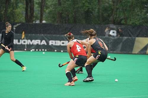 human three women playing hockey game during daytime people