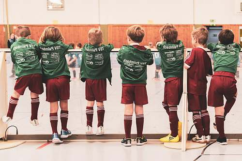 human toddlers wearing sports jersey suit standing near white wall clothing