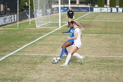 human two girls playing soccer during daytime people