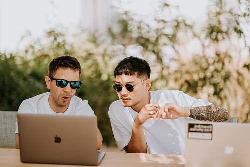 human two men using MacBooks people