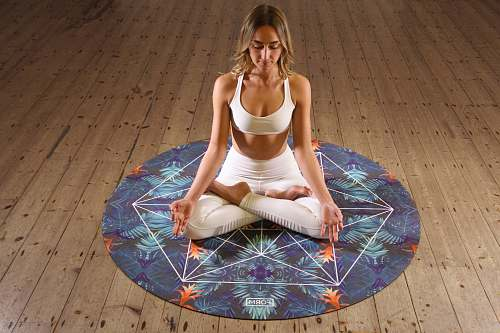 human woman sitting on round multicolored mat doing yoga people
