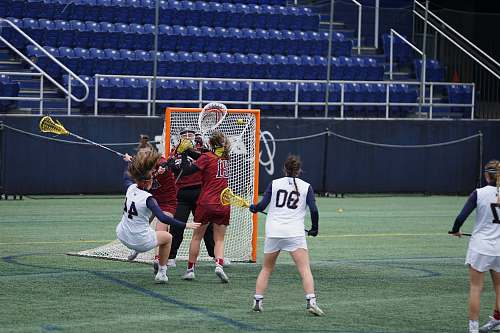 people women playing lacrosse on field during daytime human