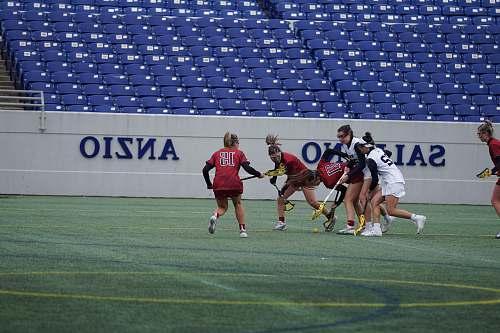 human women playing lacrosse on field people