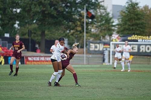 human women playing soccer at daytime people