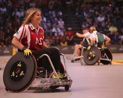 sports focus photo of woman in red and white polo shirt with black pants in ice wheelchair wheelchair