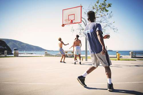 people four men playing basketball hoop