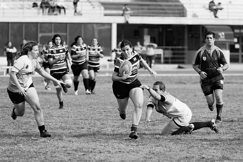 black-and-white grayscale photo of women playing rugby football team