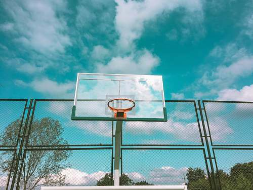 sports green and orange basketball hoop near green chain link fence under white and blue skies during daytime team