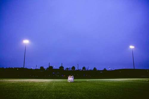 blue team hug on football field sports