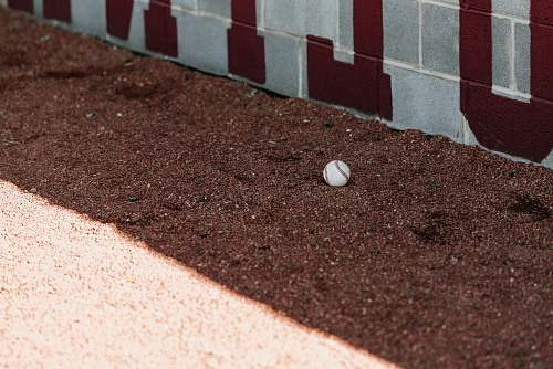 sports white marble toy on soil soil