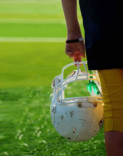 helmet shallow focus photography of football player holding helmet american football
