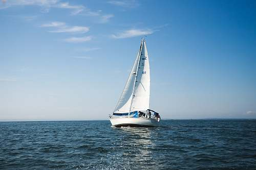 vessel blue and white sailboat on ocean during daytime sailboat
