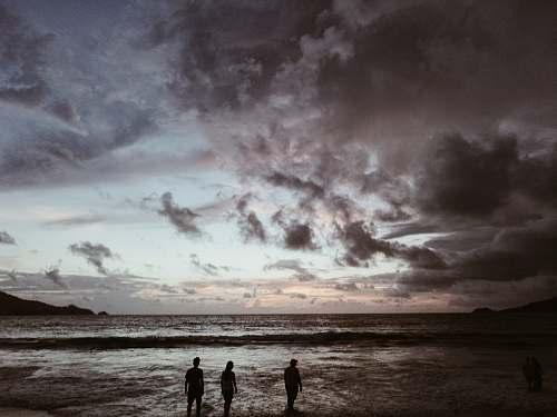 water silhouette of three people on seashore under gray cloudy skies sea