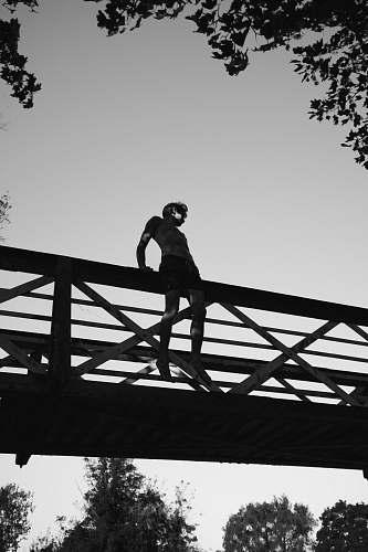 silhouette grayscale photography of man sitting on edge of bridge bridge