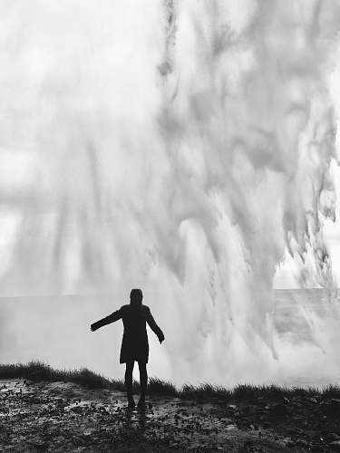 person grayscale photography of person standing in front of splashing water waves grey