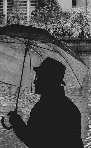 umbrella grayscale silhotte of man holding umbrella canopy