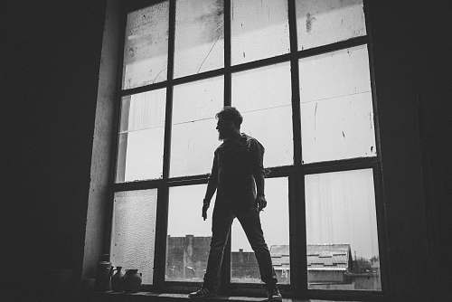 people man standing against the glass window grayscale photography grey