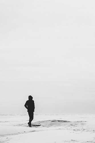 human man wearing hoodie standing on snow covered field during daytime person