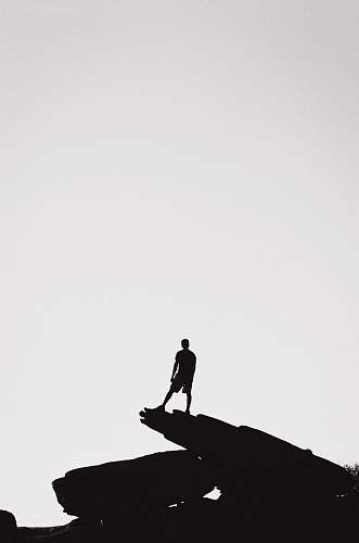 silhouette person standing in a rock formation grey-scale photography person