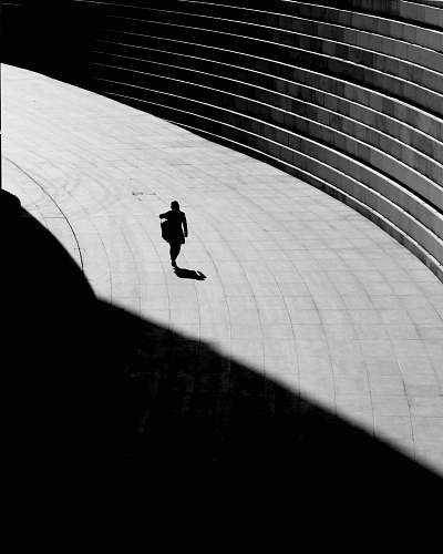 photo silhouette silhouette of a person walking on gray concrete floor shadow free for commercial use images