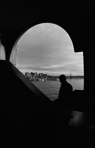 building silhouette of man near body of water architecture