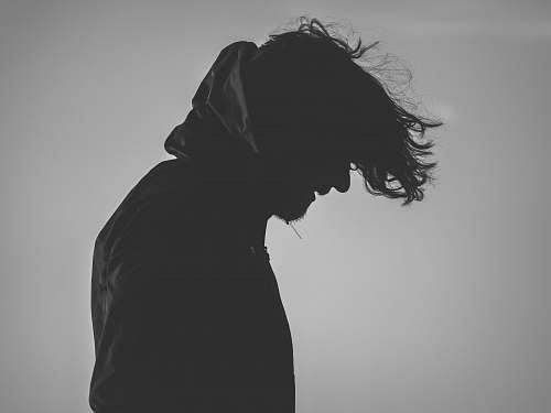 silhouette silhouette of man wearing hoodie looking down grey