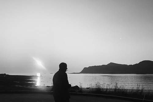 nature silhouette of person near body of water grey