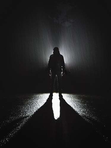 person silhouette of person standing on road during rain people