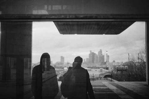 human silhouette of two people on glass grey