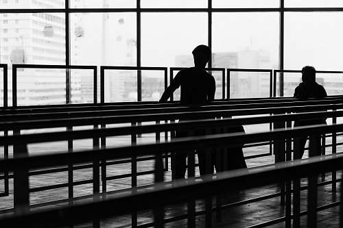 person silhouette of two person inside glass building people
