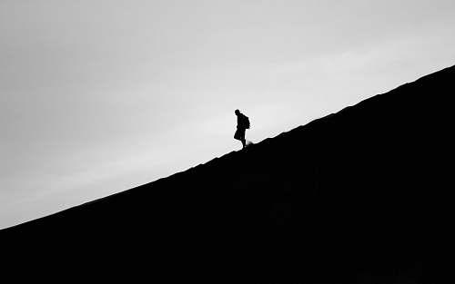 silhouette silhouette photo of person walking on mountain grey