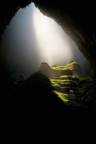vietnam person on top of rock formation inside cave sun ray