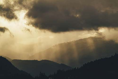 nature photo of crepuscular rays on mountains light