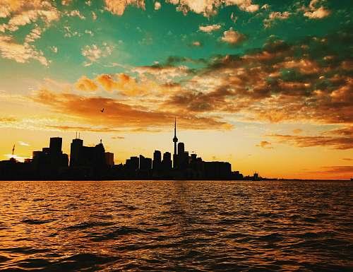 sunset body of water across city buildings during sunset dusk