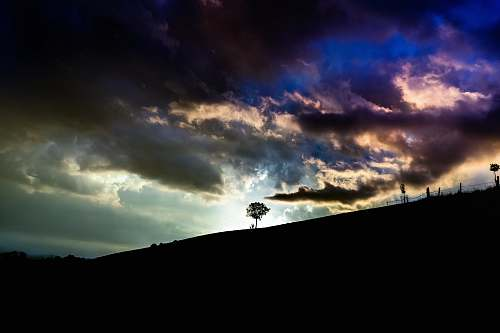 sky silhouette of tree on top of hill under cloudy sky nature