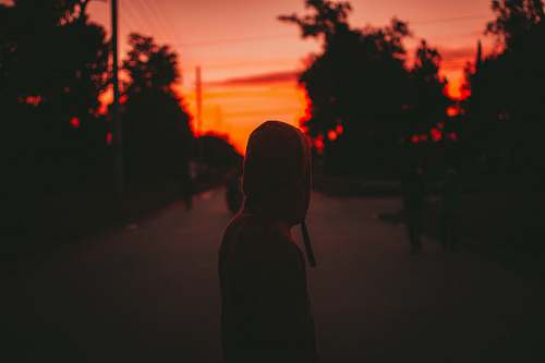 light person wearing hoodie standing on road nature