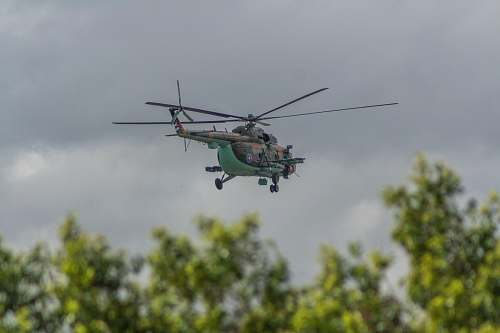 vehicle green helicopter flying under cloudy sky transportation