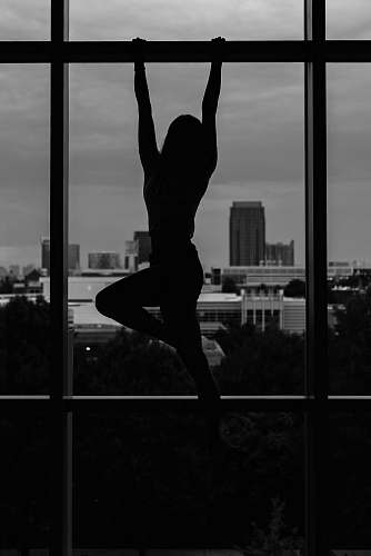 person girl hanging on steel beam black-and-white