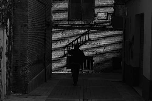 people grayscale photography of man carrying ladder black-and-white