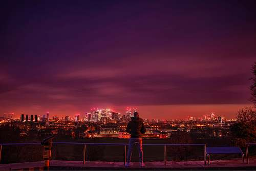 person man standing and facing city during night time nature