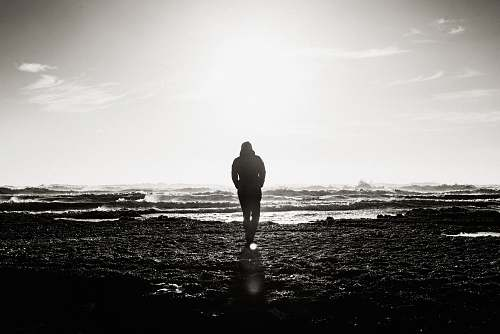 person man standing near ocean grayscale photography people