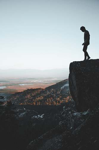 person man standing on cliff people